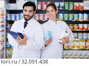 Купить «pharmacist and expert standing near shelves with medicines», фото № 32091438, снято 28 февраля 2018 г. (c) Яков Филимонов / Фотобанк Лори