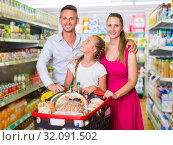 Portrait of customers which is standing with full trolley of goods. Стоковое фото, фотограф Яков Филимонов / Фотобанк Лори