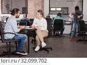 Купить «Girl and young man talking in coworking space», фото № 32099702, снято 16 марта 2019 г. (c) Яков Филимонов / Фотобанк Лори
