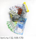 Купить «Высокие цены на лекарства. Тележка для покупок, наполненная лекарствами, стоит на денежных купюрах. Изображение на белом фоне», фото № 32109170, снято 31 августа 2019 г. (c) Ekaterina M / Фотобанк Лори