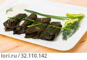 Купить «Tasty grape rolls in leaves at plate, traditional dish of Bulgarian cuisine», фото № 32110142, снято 28 марта 2020 г. (c) Яков Филимонов / Фотобанк Лори
