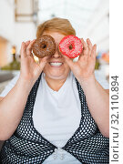 Купить «Fat woman holding doughnuts instead of eyes», фото № 32110894, снято 24 мая 2019 г. (c) Tryapitsyn Sergiy / Фотобанк Лори