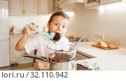 Купить «Young boy tastes melted chocolate in a bowl», фото № 32110942, снято 6 марта 2019 г. (c) Tryapitsyn Sergiy / Фотобанк Лори