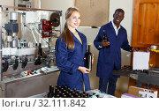 Купить «Woman and man workers packing bottles with wine in box at winery production», фото № 32111842, снято 12 сентября 2018 г. (c) Яков Филимонов / Фотобанк Лори