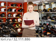 Купить «Woman choosing new motorbike», фото № 32111886, снято 16 января 2019 г. (c) Яков Филимонов / Фотобанк Лори