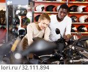 Portrait of enthusiastic man and woman looking new motorbike at motosalon showroom. Стоковое фото, фотограф Яков Филимонов / Фотобанк Лори