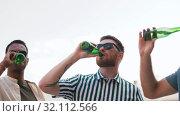 Купить «happy male friends drinking beer at rooftop party», видеоролик № 32112566, снято 27 июля 2019 г. (c) Syda Productions / Фотобанк Лори