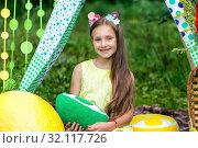 Lovely girl with picnic basket sitting in meadow in a tent. Стоковое фото, фотограф Евгений Ткачёв / Фотобанк Лори