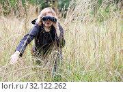Женщина наблюдает в бинокль, раздвинув рукой высокую траву на болоте. Стоковое фото, фотограф Кекяляйнен Андрей / Фотобанк Лори