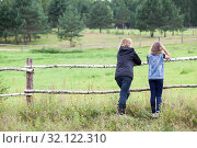 Mother and her young daughter enjoying nature in countryside, standing together, rear view, copyspace. Стоковое фото, фотограф Кекяляйнен Андрей / Фотобанк Лори