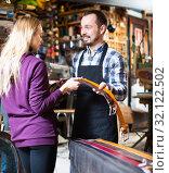 Купить «Worker offering belts to female», фото № 32122502, снято 17 октября 2019 г. (c) Яков Филимонов / Фотобанк Лори