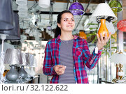 Купить «Woman in lighter shop is choosing stylish and modern lamp», фото № 32122622, снято 16 февраля 2017 г. (c) Яков Филимонов / Фотобанк Лори
