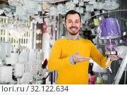 Купить «Young male in lighter shop is choosing stylish and modern lamp», фото № 32122634, снято 16 февраля 2017 г. (c) Яков Филимонов / Фотобанк Лори