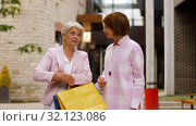 senior women with shopping bags walking in city. Стоковое видео, видеограф Syda Productions / Фотобанк Лори