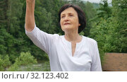 Outdoors portrait of an older woman with short dark hair and wrinkled face pointing at something during her trip to the mountains on mountain hill with green forest on background. Стоковое видео, видеограф Ольга Балынская / Фотобанк Лори