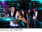 Купить «Triumphing team of laser tag winners guy and girl in foreground», фото № 32126750, снято 27 августа 2018 г. (c) Яков Филимонов / Фотобанк Лори