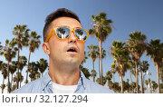 Купить «surprised man in sunglasses over palm trees», фото № 32127294, снято 22 июля 2015 г. (c) Syda Productions / Фотобанк Лори