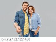 Купить «happy couple taking picture by selfie stick», фото № 32127430, снято 17 марта 2019 г. (c) Syda Productions / Фотобанк Лори