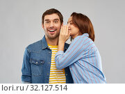 Купить «happy couple whispering over grey background», фото № 32127514, снято 17 марта 2019 г. (c) Syda Productions / Фотобанк Лори