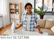 Купить «african american woman ironing bed linen at home», фото № 32127566, снято 7 апреля 2019 г. (c) Syda Productions / Фотобанк Лори
