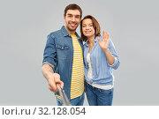 Купить «happy couple taking picture by selfie stick», фото № 32128054, снято 17 марта 2019 г. (c) Syda Productions / Фотобанк Лори