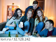 Купить «happy friends with smartphone at home party», фото № 32128242, снято 22 декабря 2018 г. (c) Syda Productions / Фотобанк Лори