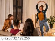 Купить «happy friends playing charades at home in evening», фото № 32128250, снято 22 декабря 2018 г. (c) Syda Productions / Фотобанк Лори