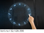 hand using interactive panel with signs of zodiac. Стоковое фото, фотограф Syda Productions / Фотобанк Лори