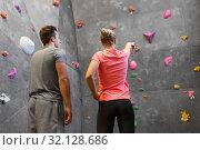 Купить «man and woman exercising at indoor climbing gym», фото № 32128686, снято 2 марта 2017 г. (c) Syda Productions / Фотобанк Лори