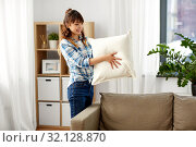 Купить «asian woman arranging sofa cushions at home», фото № 32128870, снято 13 апреля 2019 г. (c) Syda Productions / Фотобанк Лори