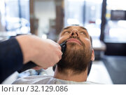 Купить «man and barber with trimmer cutting beard at salon», фото № 32129086, снято 6 апреля 2017 г. (c) Syda Productions / Фотобанк Лори