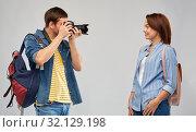 Купить «happy couple of tourists with backpacks and camera», фото № 32129198, снято 17 марта 2019 г. (c) Syda Productions / Фотобанк Лори