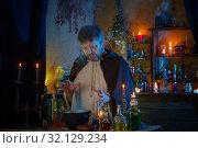 Купить «portrait of wizard with burning candles and magic potions», фото № 32129234, снято 14 августа 2019 г. (c) Майя Крученкова / Фотобанк Лори