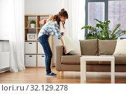 Купить «asian woman arranging sofa cushions at home», фото № 32129278, снято 13 апреля 2019 г. (c) Syda Productions / Фотобанк Лори