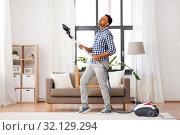 Купить «indian man with vacuum cleaner having fun at home», фото № 32129294, снято 21 апреля 2019 г. (c) Syda Productions / Фотобанк Лори