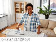Купить «african american woman ironing bed linen at home», фото № 32129630, снято 7 апреля 2019 г. (c) Syda Productions / Фотобанк Лори