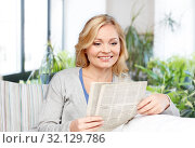 Купить «smiling woman reading newspaper at home», фото № 32129786, снято 27 ноября 2015 г. (c) Syda Productions / Фотобанк Лори