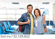 Купить «couple with air tickets and bags at airport», фото № 32129822, снято 17 марта 2019 г. (c) Syda Productions / Фотобанк Лори