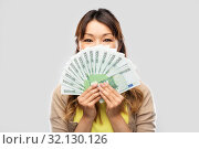 Купить «asian woman with hundred euro money banknotes», фото № 32130126, снято 11 мая 2019 г. (c) Syda Productions / Фотобанк Лори