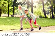 Купить «grandfather and grandson racing at summer park», фото № 32130158, снято 9 июля 2016 г. (c) Syda Productions / Фотобанк Лори
