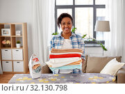 Купить «african american woman with ironed linen at home», фото № 32130798, снято 7 апреля 2019 г. (c) Syda Productions / Фотобанк Лори