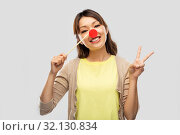 Купить «asian woman with red clown nose showing peace», фото № 32130834, снято 11 мая 2019 г. (c) Syda Productions / Фотобанк Лори