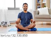 Купить «indian man meditating in lotus pose at home», фото № 32130850, снято 19 мая 2019 г. (c) Syda Productions / Фотобанк Лори