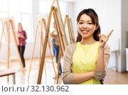 Купить «happy asian woman pointing finger up», фото № 32130962, снято 11 мая 2019 г. (c) Syda Productions / Фотобанк Лори