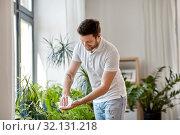 Купить «man cleaning houseplant's leaves at home», фото № 32131218, снято 22 мая 2019 г. (c) Syda Productions / Фотобанк Лори