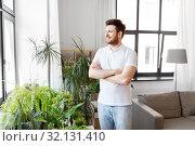 Купить «smiling man with houseplants at home», фото № 32131410, снято 22 мая 2019 г. (c) Syda Productions / Фотобанк Лори