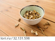 Купить «dried mushrooms in bowl on wooden background», фото № 32131598, снято 13 сентября 2018 г. (c) Syda Productions / Фотобанк Лори