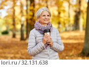 Купить «old woman with hot drink in tumbler at autumn park», фото № 32131638, снято 14 октября 2018 г. (c) Syda Productions / Фотобанк Лори
