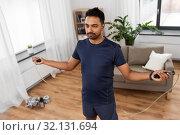 Купить «indian man exercising with jump rope at home», фото № 32131694, снято 19 мая 2019 г. (c) Syda Productions / Фотобанк Лори