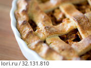 Купить «close up of apple pie in mold on wooden table», фото № 32131810, снято 23 августа 2018 г. (c) Syda Productions / Фотобанк Лори